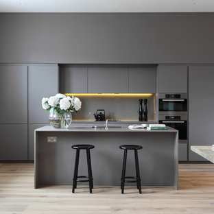 This is an example of a contemporary kitchen/diner in London with flat-panel cabinets, grey cabinets, grey splashback, stainless steel appliances, light hardwood flooring and an island.