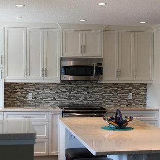 Große Klassische Wohnküche in U-Form mit Unterbauwaschbecken, Schrankfronten im Shaker-Stil, weißen Schränken, Kalkstein-Arbeitsplatte, bunter Rückwand, Rückwand aus Stäbchenfliesen, Küchengeräten aus Edelstahl und Kücheninsel in Calgary
