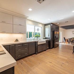 マイアミのカントリー風おしゃれなキッチン (エプロンフロントシンク、シェーカースタイル扉のキャビネット、人工大理石カウンター、黒い調理設備、グレーのキャビネット、白いキッチンパネル、無垢フローリング、茶色い床、白いキッチンカウンター) の写真