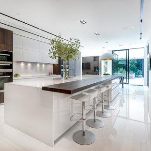 Imagen de cocina comedor de galera, moderna, extra grande, con armarios con paneles lisos, puertas de armario blancas, electrodomésticos de acero inoxidable, suelo de baldosas de porcelana y una isla