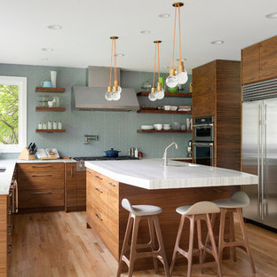 Photo of a midcentury kitchen in Minneapolis with a double-bowl sink, flat-panel cabinets, medium wood cabinets, blue splashback, stainless steel appliances, light hardwood floors, with island and white benchtop.
