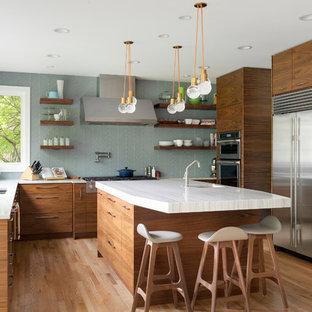 Imagen de cocina retro con fregadero de doble seno, armarios con paneles lisos, puertas de armario de madera oscura, salpicadero azul, electrodomésticos de acero inoxidable, suelo de madera clara, una isla y encimeras blancas