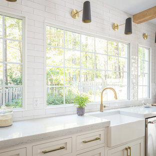 ローリーの中くらいのカントリー風おしゃれなキッチン (エプロンフロントシンク、フラットパネル扉のキャビネット、白いキャビネット、木材カウンター、白いキッチンパネル、サブウェイタイルのキッチンパネル、パネルと同色の調理設備、淡色無垢フローリング、白いキッチンカウンター) の写真