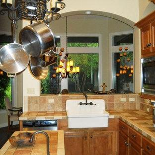 ヒューストンの中くらいのトラディショナルスタイルのおしゃれなキッチン (エプロンフロントシンク、レイズドパネル扉のキャビネット、中間色木目調キャビネット、タイルカウンター、マルチカラーのキッチンパネル、レンガのキッチンパネル、シルバーの調理設備、スレートの床) の写真