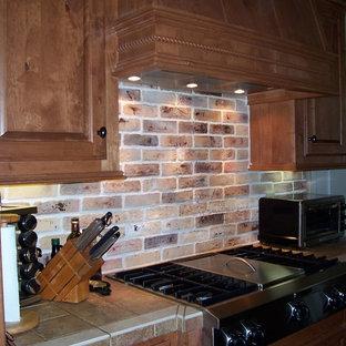 ハンティントンの中サイズのトランジショナルスタイルのおしゃれなキッチン (エプロンフロントシンク、レイズドパネル扉のキャビネット、中間色木目調キャビネット、タイルカウンター、マルチカラーのキッチンパネル、シルバーの調理設備の、スレートの床、レンガのキッチンパネル) の写真
