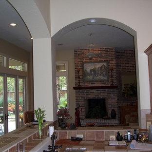ヒューストンの中サイズのトランジショナルスタイルのおしゃれなキッチン (エプロンフロントシンク、レイズドパネル扉のキャビネット、中間色木目調キャビネット、タイルカウンター、マルチカラーのキッチンパネル、レンガのキッチンパネル、シルバーの調理設備の、スレートの床) の写真