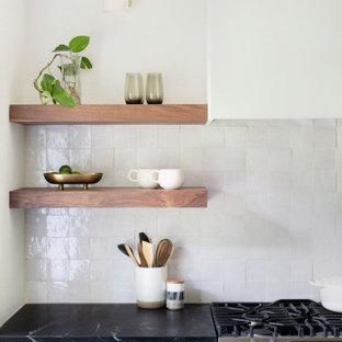 オースティンの中くらいの北欧スタイルのおしゃれなキッチン (アンダーカウンターシンク、フラットパネル扉のキャビネット、黒いキャビネット、ソープストーンカウンター、白いキッチンパネル、セラミックタイルのキッチンパネル、シルバーの調理設備、淡色無垢フローリング、ベージュの床、黒いキッチンカウンター) の写真