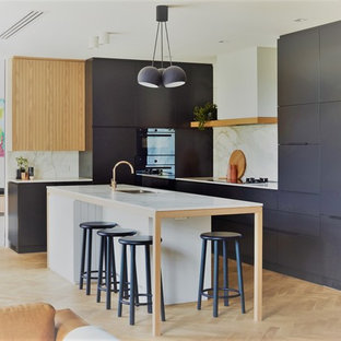 Design ideas for a contemporary l-shaped kitchen in Adelaide with an undermount sink, flat-panel cabinets, grey cabinets, white splashback, panelled appliances, light hardwood floors, with island, beige floor and white benchtop.