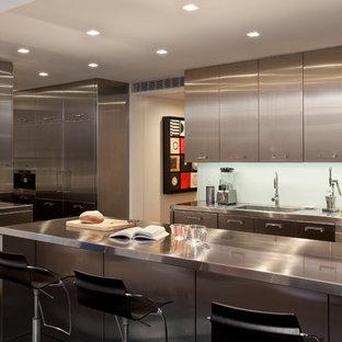 Aménagement d'une cuisine contemporaine en U avec un évier intégré, un placard à porte plane, une façade en inox, un plan de travail en inox, une crédence en feuille de verre, un électroménager en acier inoxydable, une péninsule, une crédence bleue et un sol en bois foncé.