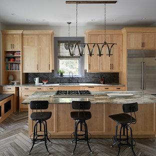 他の地域の大きいトランジショナルスタイルのおしゃれなアイランドキッチン (シングルシンク、シェーカースタイル扉のキャビネット、淡色木目調キャビネット、御影石カウンター、シルバーの調理設備の、磁器タイルの床、黒いキッチンパネル、サブウェイタイルのキッチンパネル、マルチカラーのキッチンカウンター、茶色い床) の写真