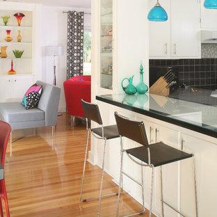 Design ideas for a medium sized contemporary l-shaped kitchen/diner in Charleston with flat-panel cabinets, white cabinets, glass worktops, grey splashback, glass tiled splashback, medium hardwood flooring and no island.