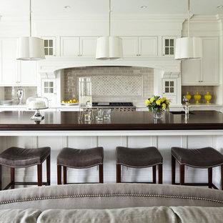 Пример оригинального дизайна: большая угловая кухня-гостиная в стиле современная классика с деревянной столешницей, фасадами с утопленной филенкой, белыми фасадами, серым фартуком, врезной раковиной, фартуком из керамической плитки, техникой из нержавеющей стали, деревянным полом, островом и коричневой столешницей