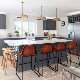 Design ideas for a classic l-shaped kitchen in Gloucestershire with a belfast sink, shaker cabinets, grey cabinets, grey splashback, stainless steel appliances, an island, beige floors and white worktops.