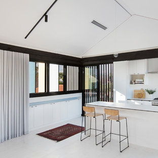 This is an example of a medium sized beach style open plan kitchen in Perth with white cabinets, tile countertops, white splashback, ceramic splashback, white appliances, plywood flooring, an island and white floors.