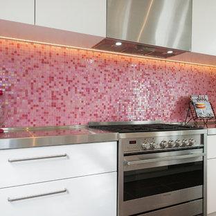 Imagen de cocina de galera, contemporánea, pequeña, con fregadero bajoencimera, armarios con paneles lisos, puertas de armario blancas, encimera de acrílico, salpicadero rosa, salpicadero con mosaicos de azulejos, electrodomésticos de acero inoxidable, suelo de baldosas de cerámica y una isla