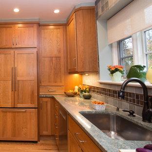 Mittelgroße Klassische Küche in U-Form mit Unterbauwaschbecken, Schrankfronten mit vertiefter Füllung, hellbraunen Holzschränken, Granit-Arbeitsplatte, Küchenrückwand in Grün, Rückwand aus Keramikfliesen, Küchengeräten aus Edelstahl und hellem Holzboden in Philadelphia