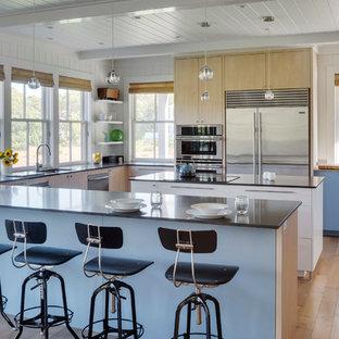 Foto di una grande cucina minimalista con lavello sottopiano, ante lisce, elettrodomestici in acciaio inossidabile, parquet chiaro, ante blu, isola e pavimento marrone