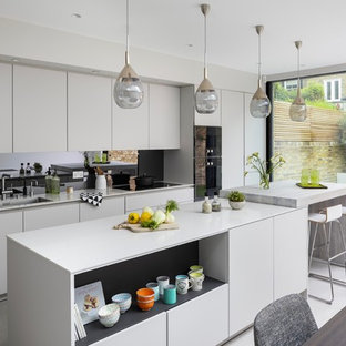 Design ideas for an expansive contemporary single-wall kitchen in London with flat-panel cabinets, grey cabinets, wood benchtops, grey splashback, mirror splashback, panelled appliances, ceramic floors, with island, grey floor, grey benchtop and an undermount sink.