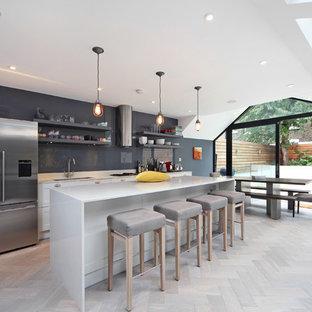 Inredning av ett modernt stort kök och matrum, med en undermonterad diskho, granitbänkskiva, grått stänkskydd, rostfria vitvaror, ljust trägolv, en köksö, öppna hyllor, grå skåp och glaspanel som stänkskydd
