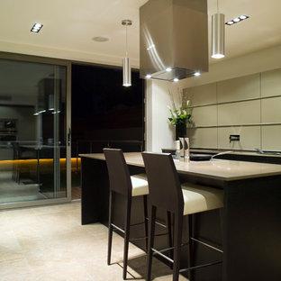 Esempio di una cucina minimalista di medie dimensioni con ante lisce, ante nere, top in superficie solida, paraspruzzi verde, paraspruzzi con piastrelle di metallo, pavimento in pietra calcarea e isola