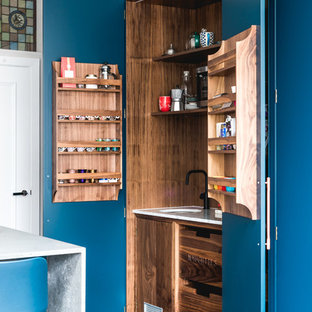 Photo of a contemporary kitchen pantry in London with a submerged sink, blue cabinets and grey floors.