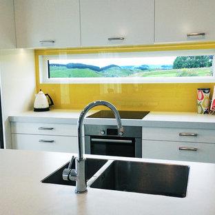 他の地域の中サイズのモダンスタイルのおしゃれなキッチン (ダブルシンク、フラットパネル扉のキャビネット、白いキャビネット、ラミネートカウンター、黄色いキッチンパネル、ガラス板のキッチンパネル、白い調理設備、コンクリートの床) の写真