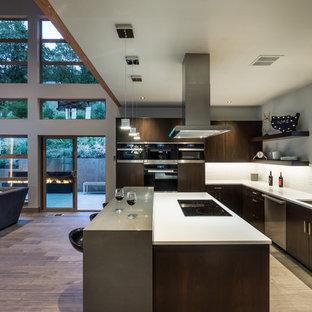 Immagine di una cucina contemporanea con lavello sottopiano, ante lisce, ante in legno bruno, paraspruzzi bianco, elettrodomestici in acciaio inossidabile e pavimento in legno massello medio