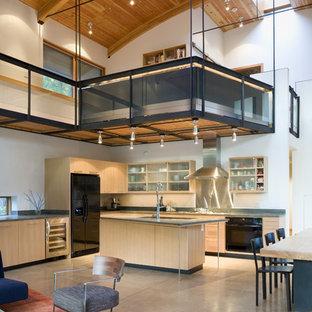 Diseño de cocina en L, actual, de tamaño medio, abierta, con electrodomésticos negros, armarios tipo vitrina, puertas de armario de madera clara, salpicadero metalizado, salpicadero de metal, encimera de acrílico, suelo de cemento y una isla