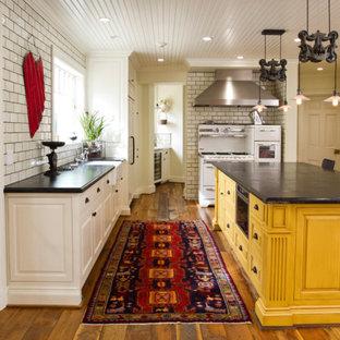 ロサンゼルスの中くらいのカントリー風おしゃれなキッチン (エプロンフロントシンク、レイズドパネル扉のキャビネット、黄色いキャビネット、白いキッチンパネル、サブウェイタイルのキッチンパネル、白い調理設備、無垢フローリング、茶色い床) の写真