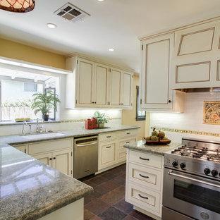 На фото: угловая кухня среднего размера в классическом стиле с полуостровом, фасадами с утопленной филенкой, гранитной столешницей, белым фартуком, фартуком из керамической плитки, техникой из нержавеющей стали, накладной раковиной и полом из сланца с