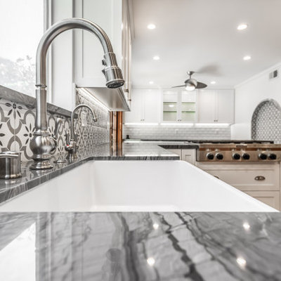 Inspiration for a mid-sized farmhouse u-shaped terra-cotta tile and red floor open concept kitchen remodel in Los Angeles with a farmhouse sink, shaker cabinets, white cabinets, quartzite countertops, gray backsplash, ceramic backsplash, stainless steel appliances, a peninsula and gray countertops