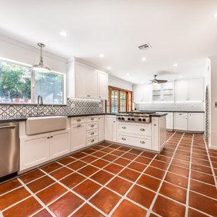 ロサンゼルスの中サイズのカントリー風おしゃれなキッチン (エプロンフロントシンク、シェーカースタイル扉のキャビネット、白いキャビネット、珪岩カウンター、グレーのキッチンパネル、セラミックタイルのキッチンパネル、シルバーの調理設備、テラコッタタイルの床、赤い床、グレーのキッチンカウンター) の写真