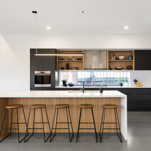 Photo of a scandinavian open plan kitchen in Melbourne with a double-bowl sink, flat-panel cabinets, black cabinets, window splashback, white appliances, concrete floors, an island, grey floor and white benchtop.
