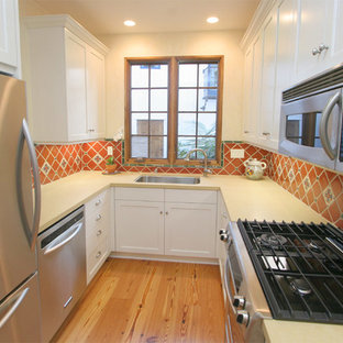 Small mediterranean enclosed kitchen designs - Inspiration for a small mediterranean u-shaped light wood floor and brown floor enclosed kitchen remodel in Santa Barbara with an undermount sink, shaker cabinets, white cabinets, quartz countertops, multicolored backsplash, mosaic tile backsplash, stainless steel appliances and no island