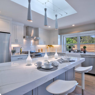 Photo of a modern l-shaped eat-in kitchen in San Francisco with a farmhouse sink, shaker cabinets, white cabinets, quartzite benchtops, white splashback, porcelain splashback, stainless steel appliances, light hardwood floors, with island and green floor.