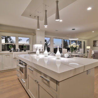 Inspiration for a modern l-shaped eat-in kitchen in San Francisco with a farmhouse sink, shaker cabinets, white cabinets, quartzite benchtops, white splashback, porcelain splashback, stainless steel appliances, light hardwood floors, with island and green floor.