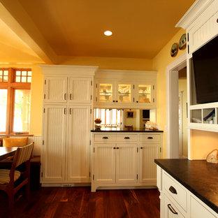 Große, Geschlossene Country Küche in U-Form mit Triple-Waschtisch, Kassettenfronten, weißen Schränken, Granit-Arbeitsplatte, bunter Rückwand, Rückwand aus Steinfliesen, Elektrogeräten mit Frontblende, braunem Holzboden und Kücheninsel in Sonstige