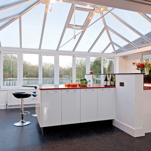 Cette image montre une cuisine design avec des portes de placard blanches, un îlot central, un placard à porte plane et un plan de travail rouge.