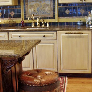 Large victorian eat-in kitchen photos - Inspiration for a large victorian u-shaped medium tone wood floor eat-in kitchen remodel in New Orleans with an undermount sink, raised-panel cabinets, distressed cabinets, granite countertops, blue backsplash, mosaic tile backsplash, paneled appliances and an island