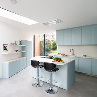 This is an example of a medium sized contemporary kitchen in London with flat-panel cabinets, blue cabinets, an island, white worktops, white splashback, a submerged sink and grey floors.