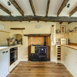 Zweizeilige Landhaus Küche ohne Insel mit Schrankfronten im Shaker-Stil, gelben Schränken, Arbeitsplatte aus Holz, Küchenrückwand in Orange, schwarzen Elektrogeräten und braunem Holzboden in Sonstige
