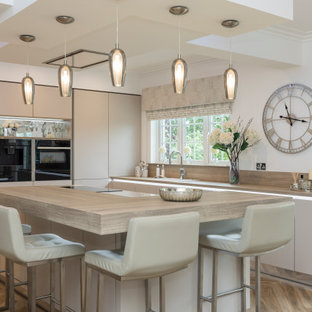 Photo of a large contemporary l-shaped enclosed kitchen in Other with flat-panel cabinets, beige cabinets, engineered stone countertops, black appliances, laminate floors, an island and white worktops.