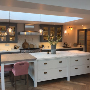 This is an example of a classic single-wall kitchen in London with a submerged sink, flat-panel cabinets, marble worktops, white splashback, marble splashback, stainless steel appliances, dark hardwood flooring, an island, brown floors and white worktops.