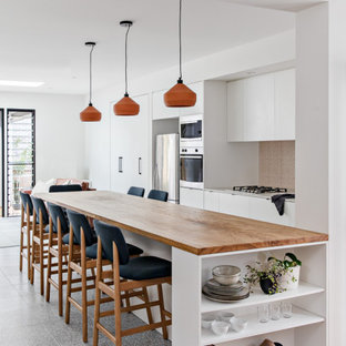 Photo of a small scandinavian galley open plan kitchen in Sydney with an undermount sink, white cabinets, wood benchtops, pink splashback, ceramic splashback, stainless steel appliances, terrazzo floors, with island, grey floor and brown benchtop.