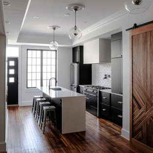 This is an example of a mid-sized contemporary galley eat-in kitchen in Baltimore with an undermount sink, flat-panel cabinets, black cabinets, quartz benchtops, white splashback, brick splashback, stainless steel appliances, medium hardwood floors, with island, brown floor, white benchtop and recessed.