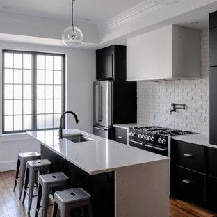 ボルチモアの中くらいのコンテンポラリースタイルのおしゃれなキッチン (アンダーカウンターシンク、フラットパネル扉のキャビネット、黒いキャビネット、クオーツストーンカウンター、白いキッチンパネル、レンガのキッチンパネル、シルバーの調理設備、無垢フローリング、茶色い床、白いキッチンカウンター、折り上げ天井) の写真