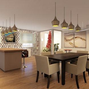Modern inredning av ett stort brun brunt kök, med en nedsänkt diskho, släta luckor, vita skåp, träbänkskiva, flerfärgad stänkskydd, stänkskydd i terrakottakakel, rostfria vitvaror, laminatgolv, en köksö och brunt golv