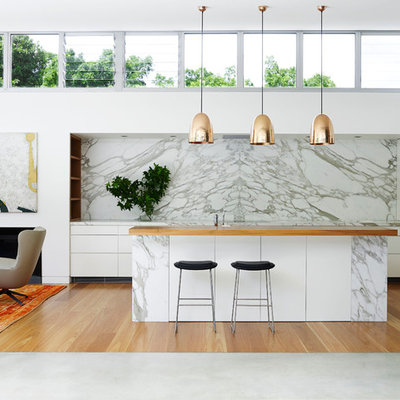 Huge trendy open concept kitchen photo in Sydney with flat-panel cabinets, white cabinets, marble countertops, an island, white backsplash and paneled appliances