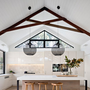 Photo of a mid-sized contemporary l-shaped kitchen in Melbourne with flat-panel cabinets, white cabinets, beige splashback, medium hardwood floors, brown floor, an undermount sink, panelled appliances and an island.