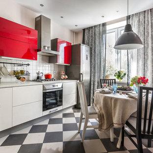 Bild på ett mellanstort, avskilt nordiskt l-kök, med släta luckor, vitt stänkskydd, rostfria vitvaror och flerfärgat golv